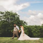 bride and groom in grassy field for outdoor wedding near kansas city