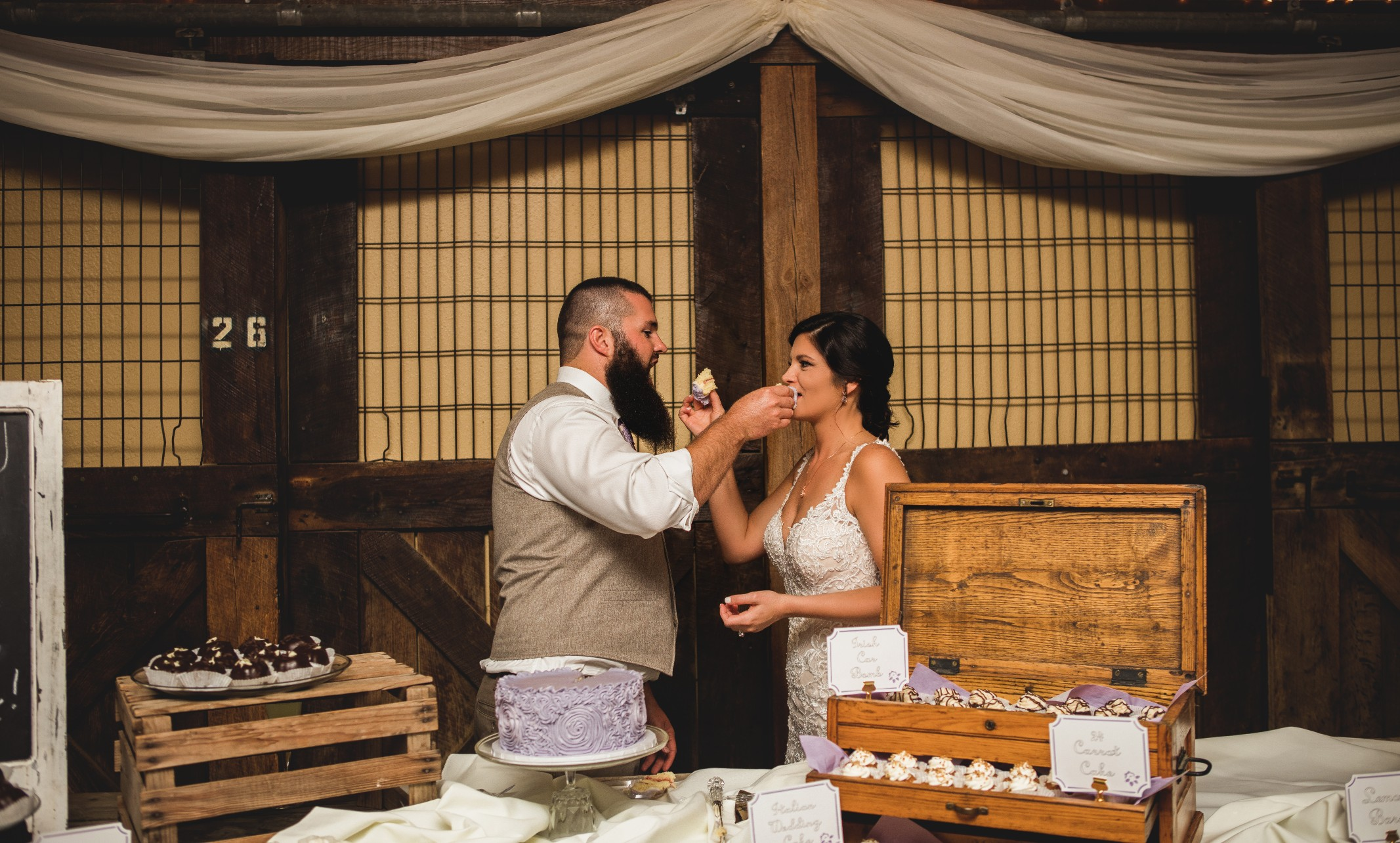 bride and groom eat cake at indoor wedding reception room at Faulkner's Ranch