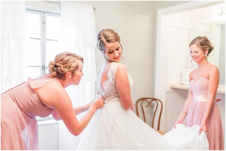 bridesmaid helping bride zip up dress for wedding at Faulkner's Ranch