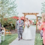 father and the bride walking down isle at outdoor wedding