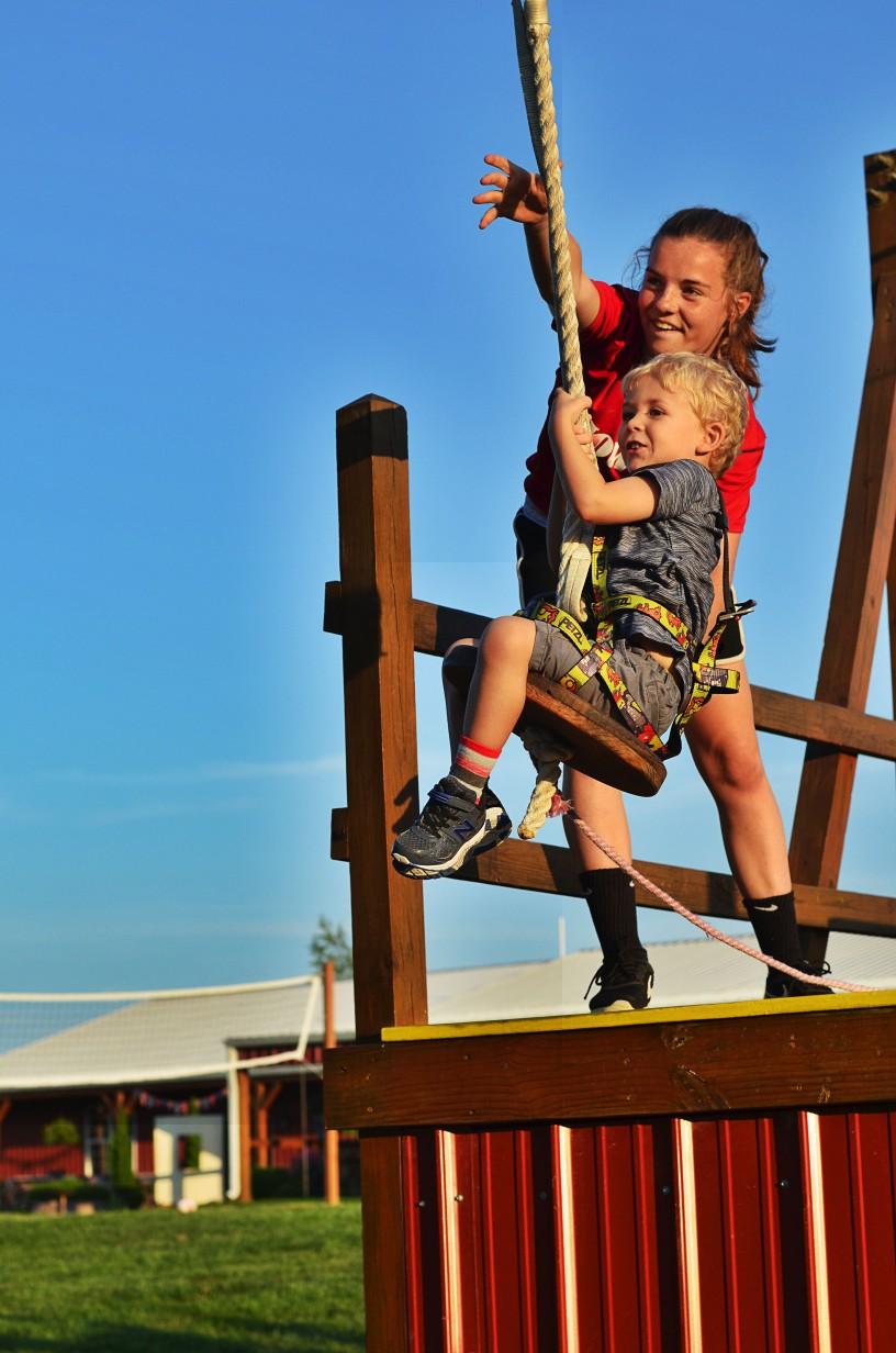 child riding on zip line